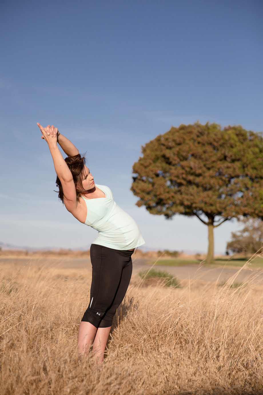 Pregnant expectant mother doing yoga in grassy field with tree