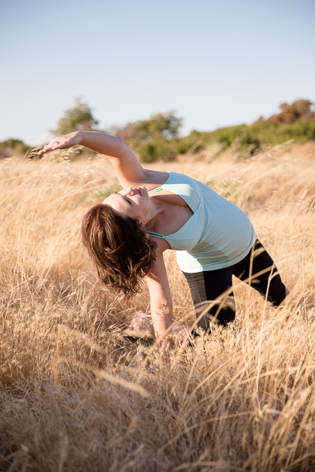 Expectant mother doing yoga in a grassy field at sunset