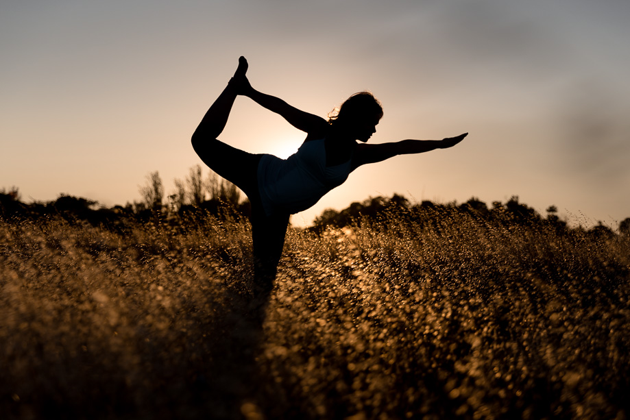 Pregnant expectant mother performing yoga pose in golden grassy field silhouetted against the setting sun