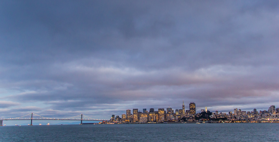 Skyline of San Francisco and the Bay Bridge as seen at dusk from aboard the California Hornblower cruise ship