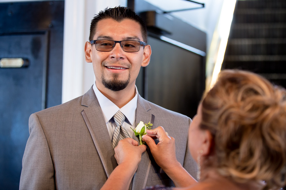 Pinning the boutonniere on the groom