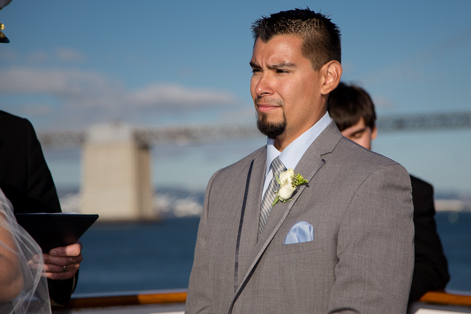 Groom looking at the bride while the captain and officiant says a few words