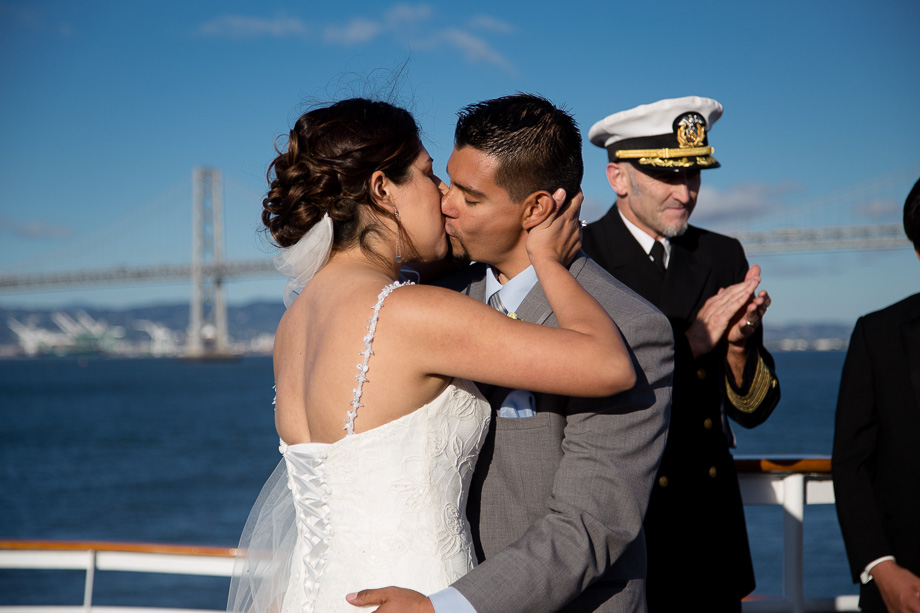Bride and groom kissing after their marriage ceremony with the captain clapping