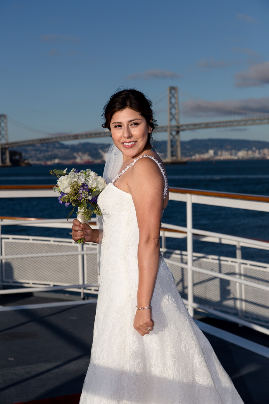 Portrait of the bride and her bouquet with the Bay Bridge in the background