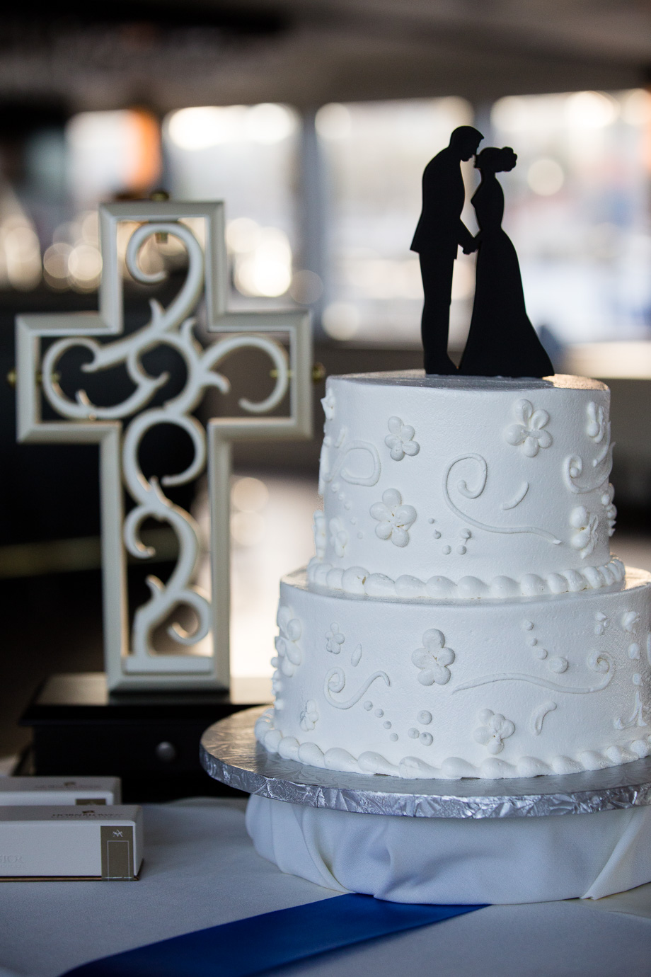 Wedding cake with silhouette cake topper and cross in background