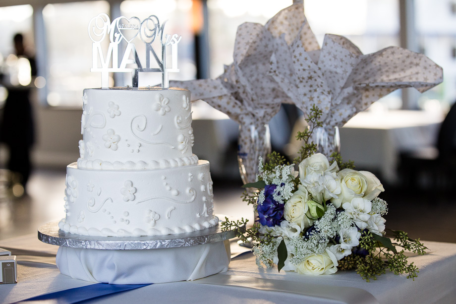 Wedding cake on table in cruise ship with bouquet next to it