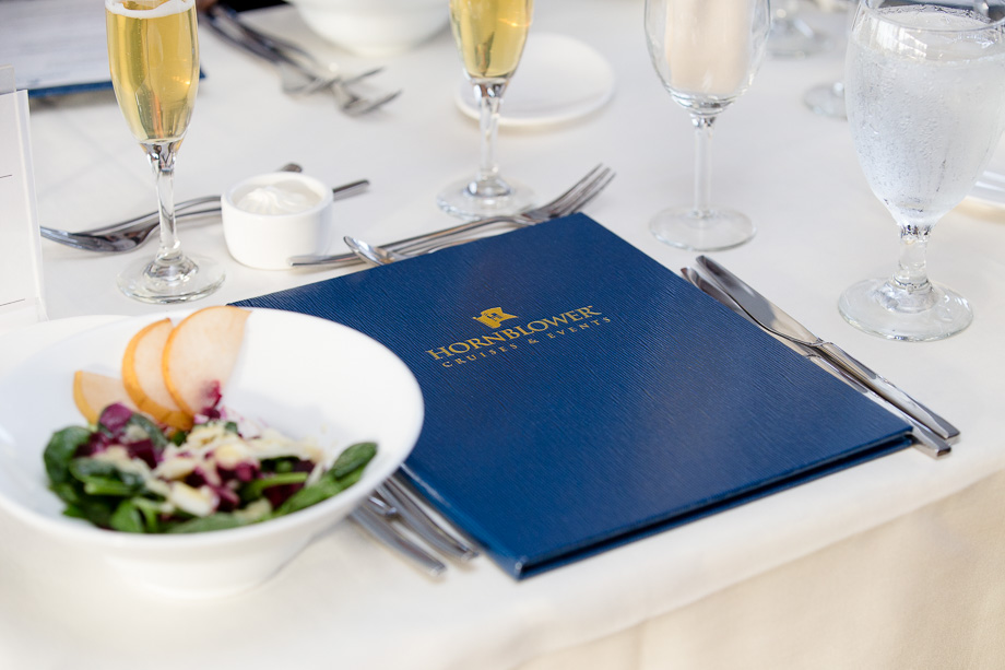 Hornblower Cruises & Events dinner menu with champagne glasses and salad