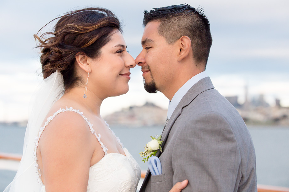 Bride and groom rubbing noses and looking at each other on board the California Hornblower cruise ship