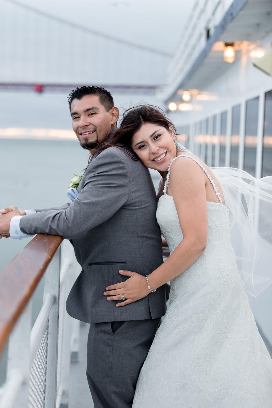 Portrait of bride behind groom on California Hornblower cruise ship with Golden Gate Bridge in the background