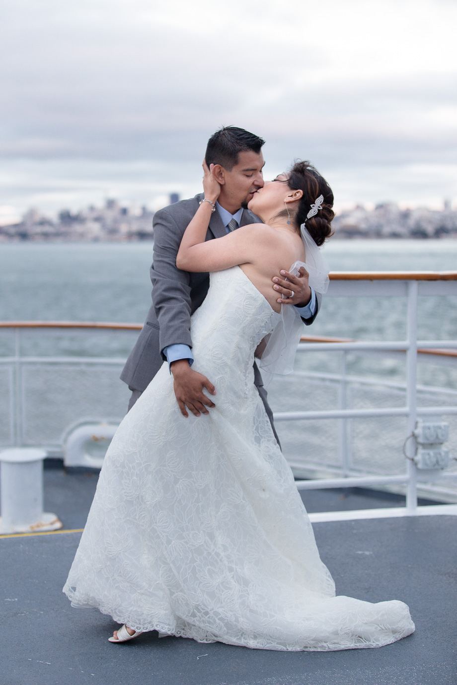 Bride and groom kissing on the deck of the California Hornblower cruise boat