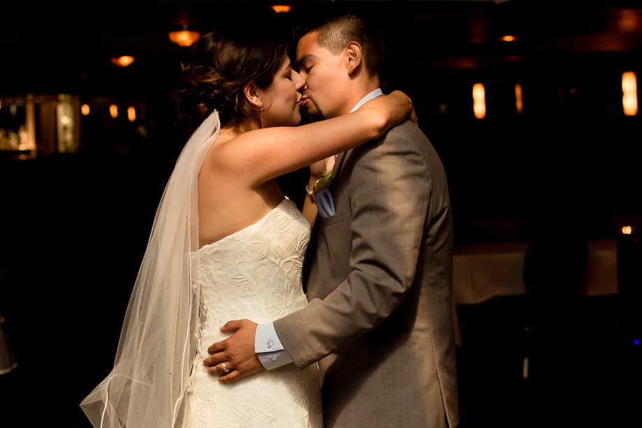 The bride and groom kissing during their first dance on the dance floor of the cruise ship