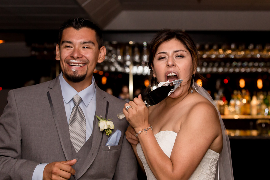 Bride licking the wedding cake knife, groom with cake smeared on his mouth