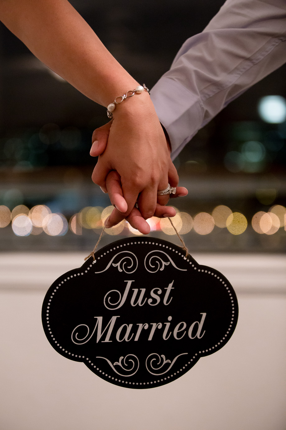Newlywed couple holding Just Married sign and showing off ring in front of a beautiful line of blurred lights