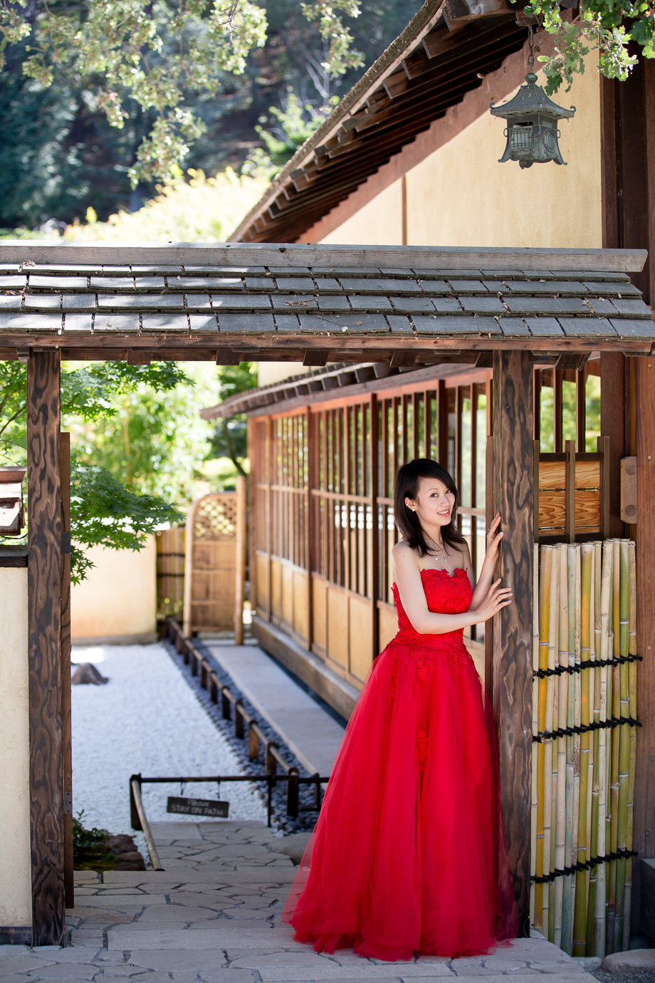 Renee in a sharp red dress leaning on a Japanese-style doorway at Hakone Gardens