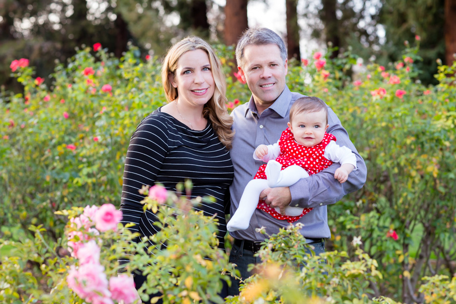 A beautiful family surrounded by pink rose bushes just before Christmas