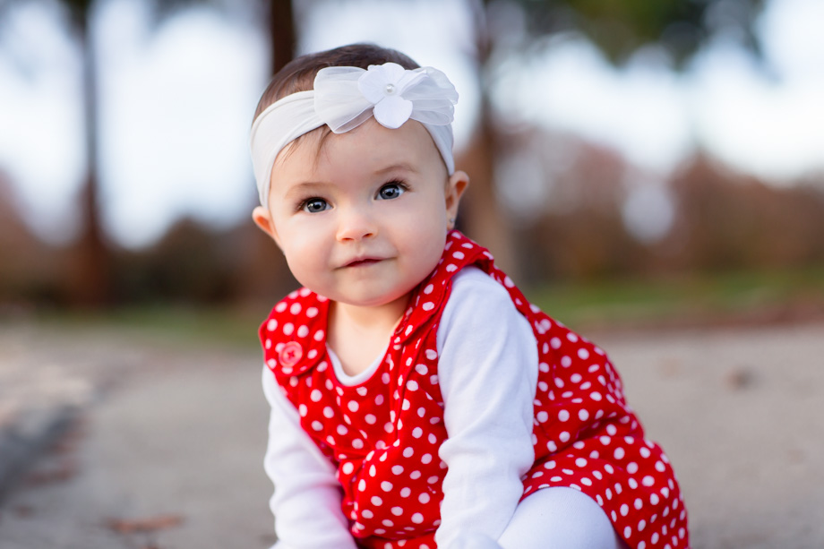 Adorable red polka dot dress and a white floral headband for the cute smiling nine-month-old baby for the family Christmas cards