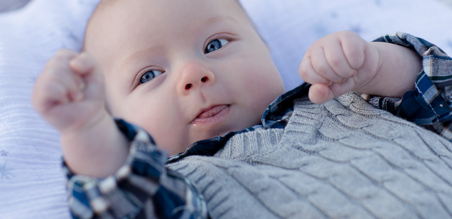 Cute 3 month old boy - big blue eyed baby boxing portrait