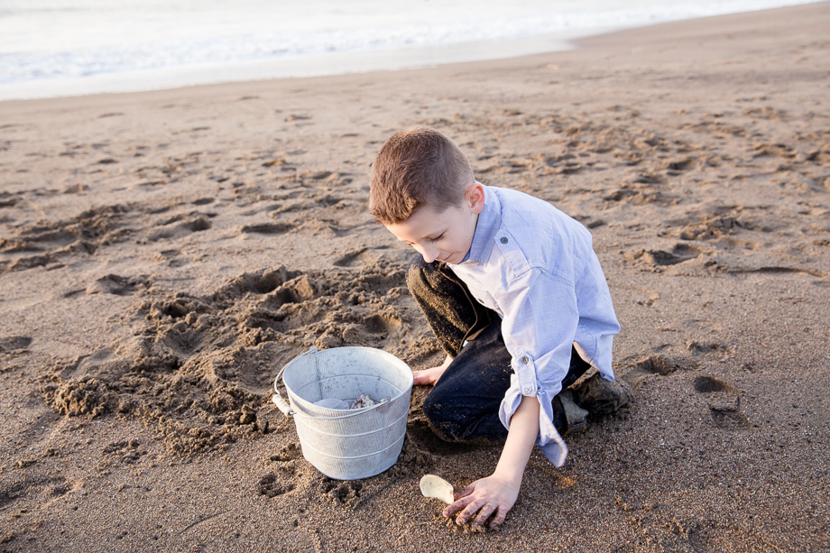 five year old boy playing sand with seashells on beaker beach