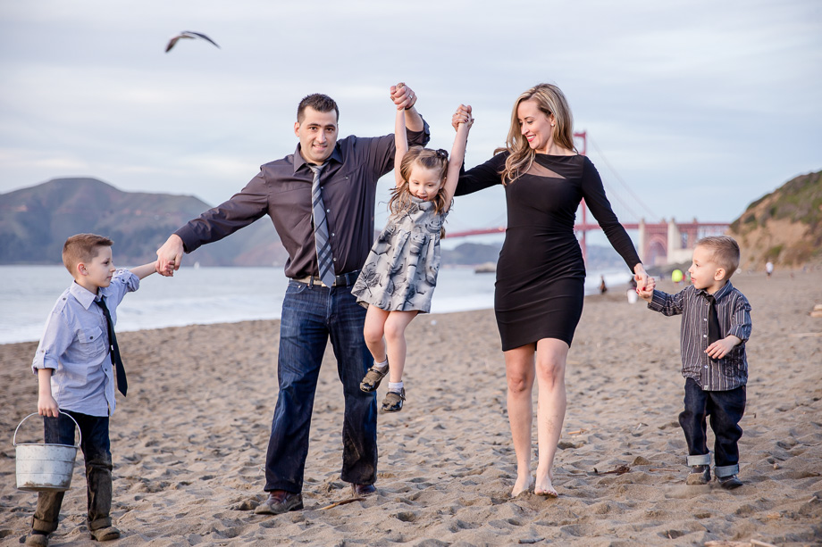 parents lifting baby girl up on the beach - a beautiful family of five