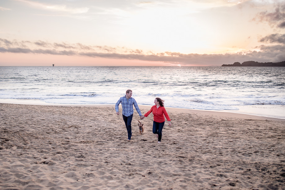 running shot of the engaged couple and their dog