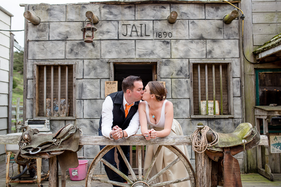 bride and groom kissing in front of a Western old jail house - long branch saloon and farms