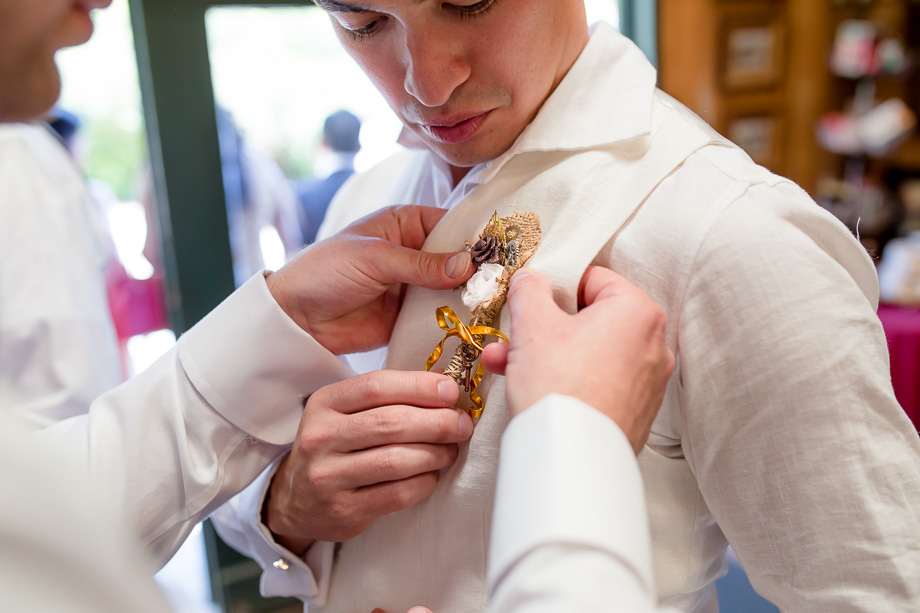 groom pinning the boutonniere handmade by the bride