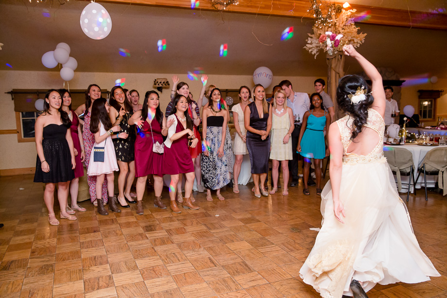 bride teasing single girls with the bouquet toss