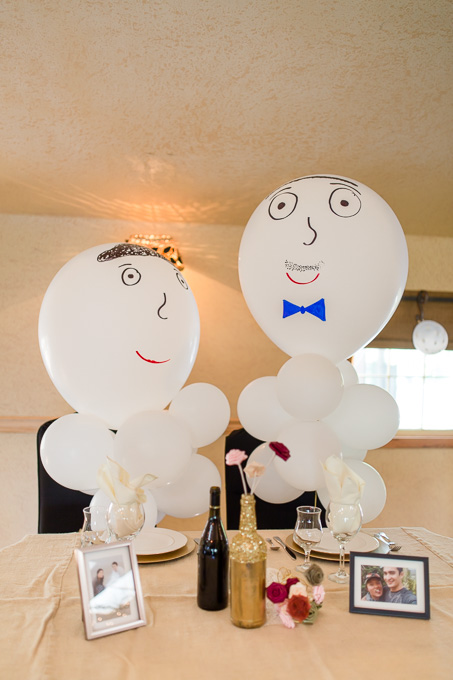 friends surprised bride and groom with two giant balloons with faces at their sweetheart table