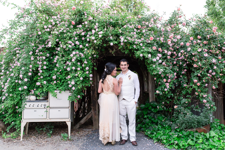 bride and groom standing under the flower tunnel at Union Hill Inn, Sonora