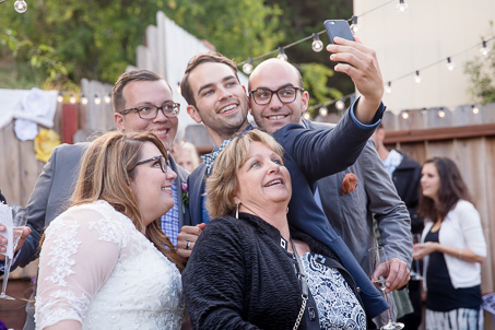 wedding guests taking a selfie with the bride and groom