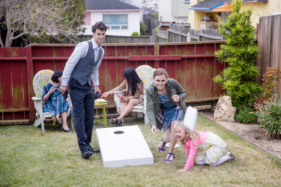 wedding guests having fun with cornhole lawn game