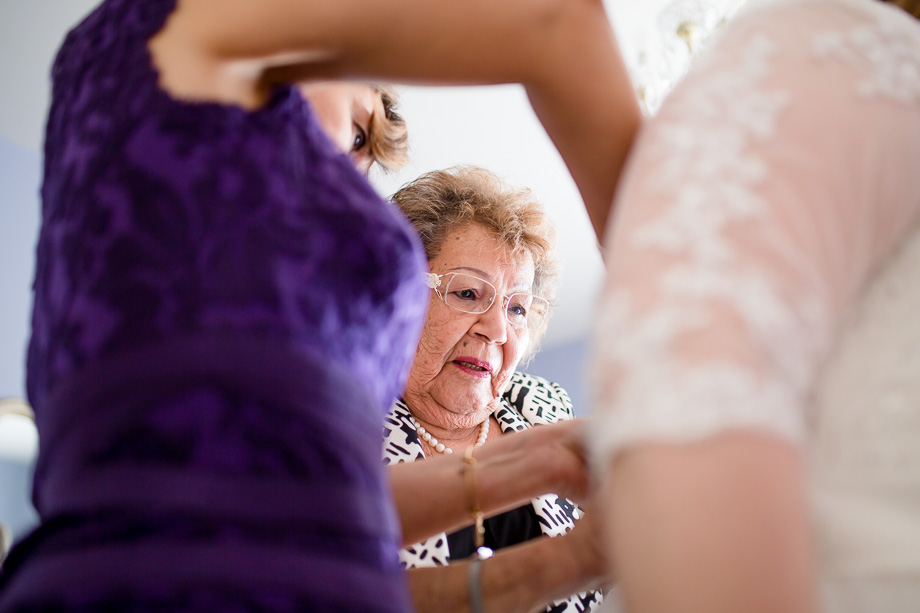 grandma zipping up the wedding dress for the bride