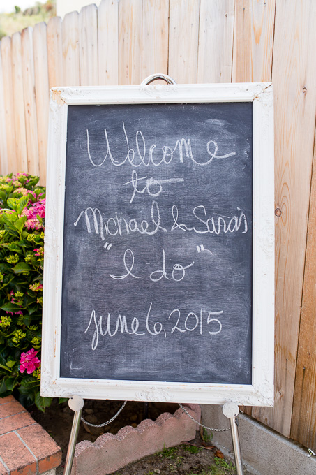 Handwritten chalkboard welcome sign for an intimate backyard wedding