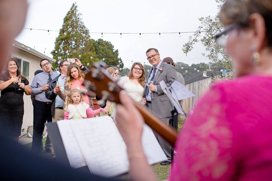 bride and groom enjoying familys surprise music performance