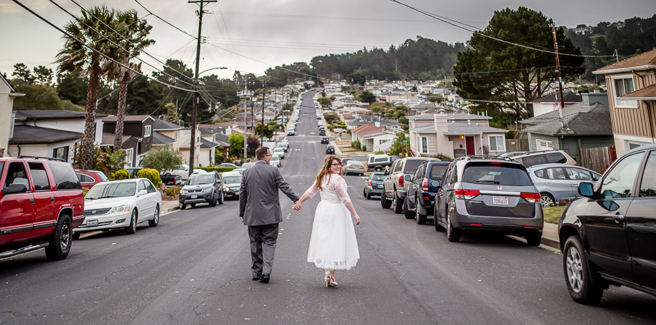 a stunning photo of bride and groom walking in front of their house