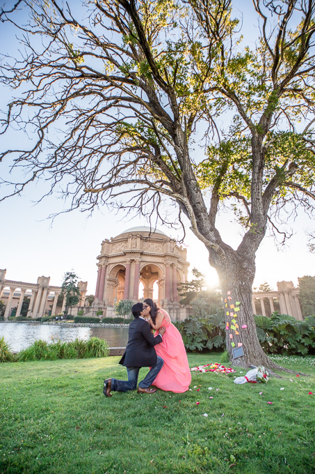 newly engaged couple kissing in front of Palace of Fine Arts after their proposal
