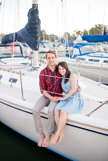 couple sitting on their own sailboat for their engagement pictures