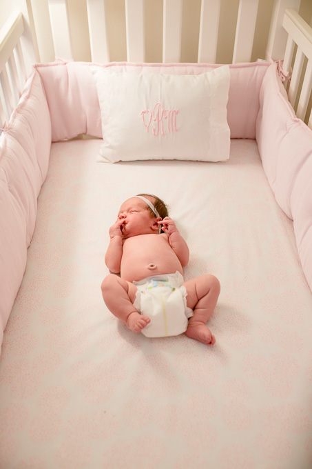 7 day old cute baby girl sleeping in her pink crib
