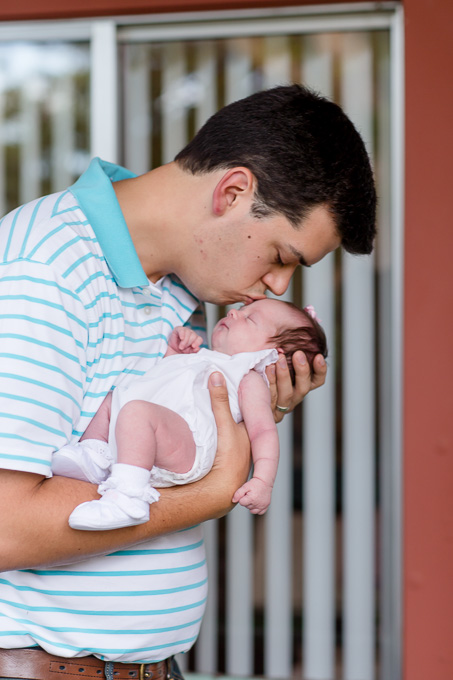 daddy giving newborn girl lots of kisses