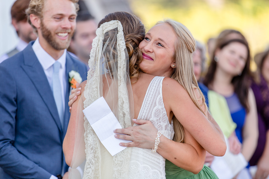 bridesmaid giving sister-in-law a warm hug during the wedding ceremony