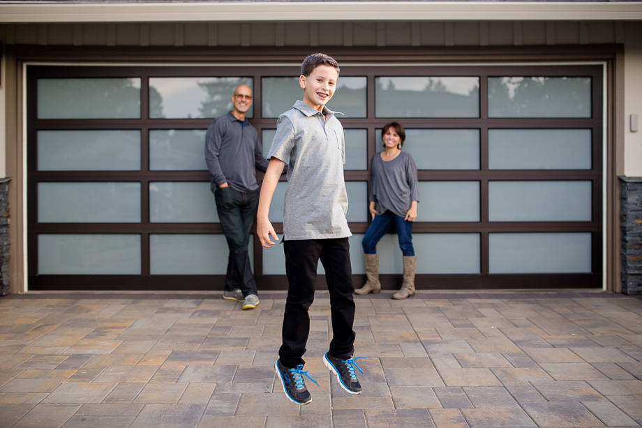 boy jumping in front of parents