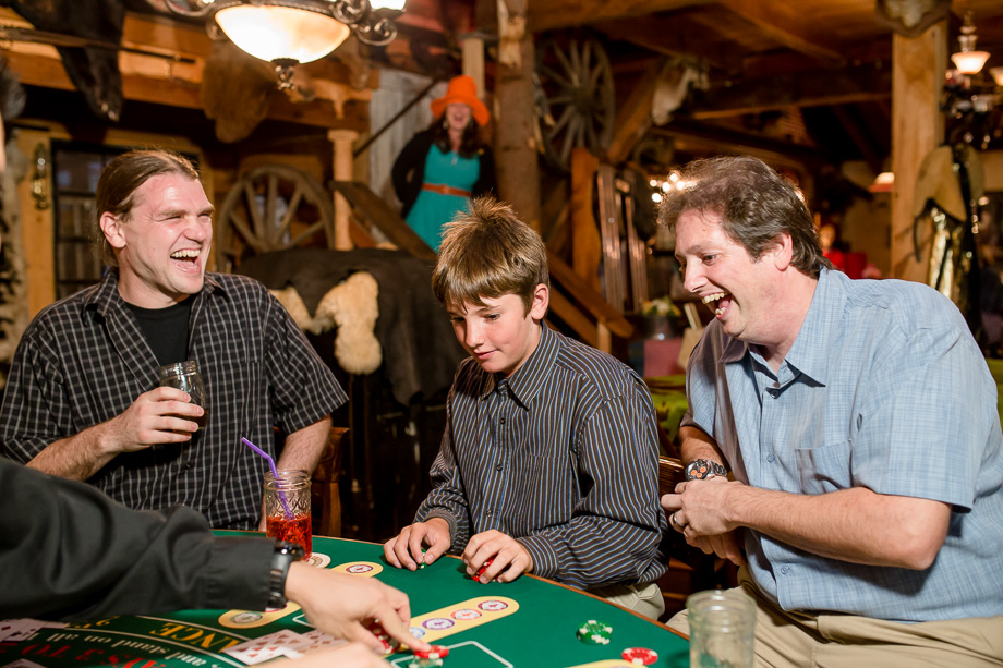 wedding guests having fun at the poker table inside the farm house at long branch saloon, half moon bay