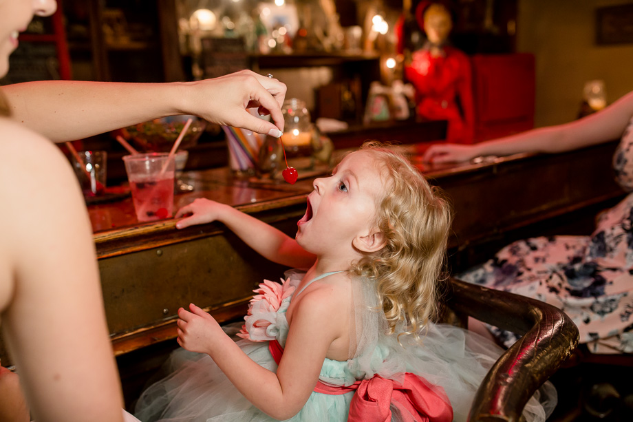 adorable hungry flower girl at the bar eating cherries