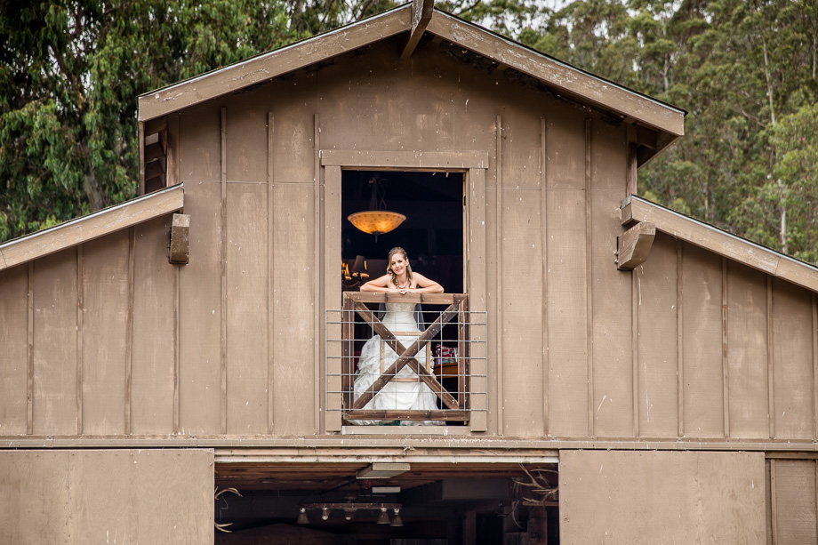 beautiful bride peeking out from the old rustic farmhouse