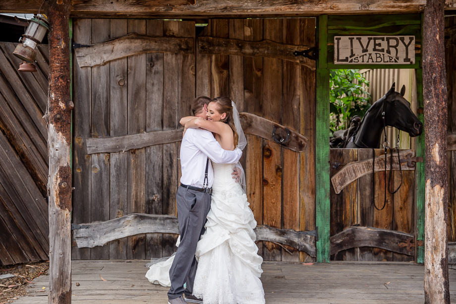 a romantic first look in front of a rustic farm house