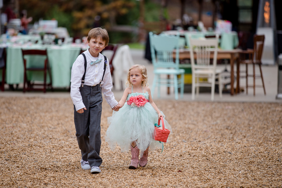 cute ring bearer and flower girl walking down the aisle