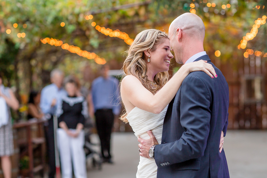 newlyweds first dance in garden with background string lighting