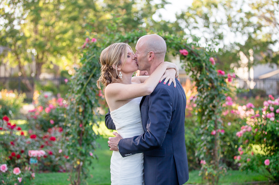 bride and groom kissing after outdoor intimate wedding ceremony at rose garden