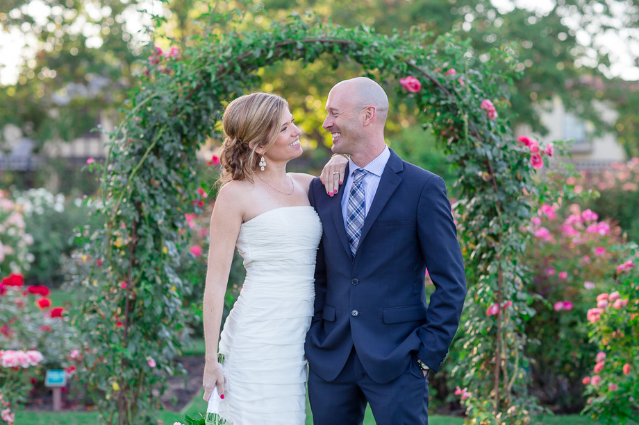 newlyweds standing in front of the arch at san jose rose garden