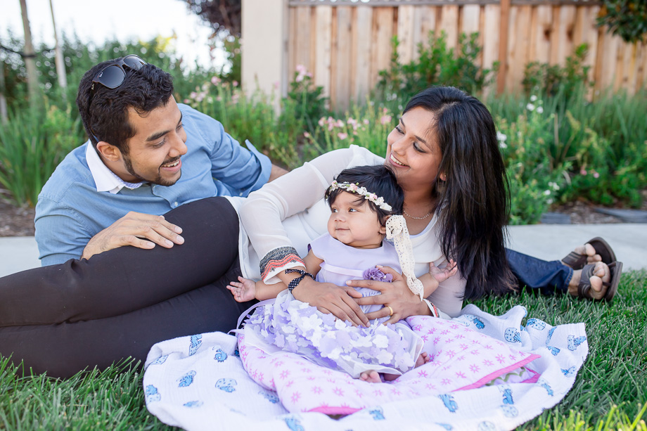 outdoor family photo of baby girl and parents in grass